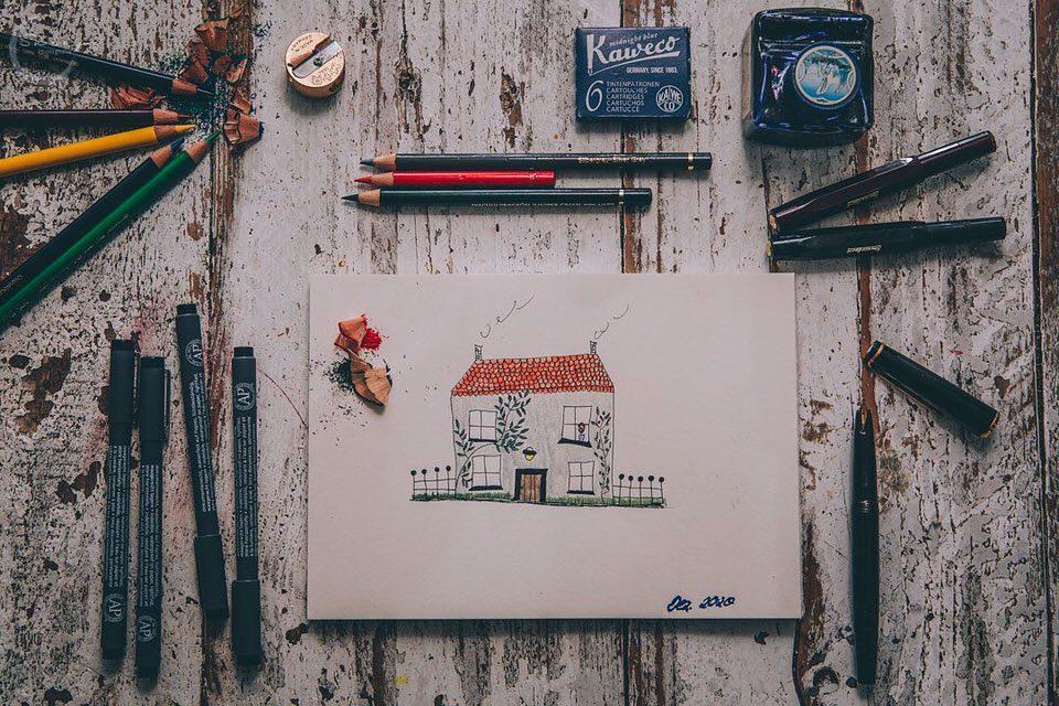 Auf einem Tisch liegen Stifte und ein Bild