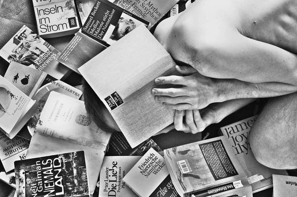 Person versteckt sich hinter einem Buch