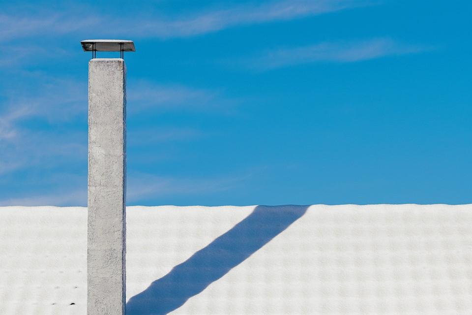 Dach mit Schornstein vor blauem Himmel