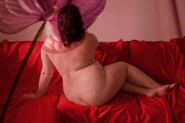 Nackte Frau auf einem Sofa mit dem Rücken der Kamera zugewandt