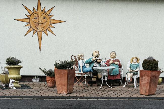 An einer Hauswand sitzen Figuren an einem Miniaturtisch