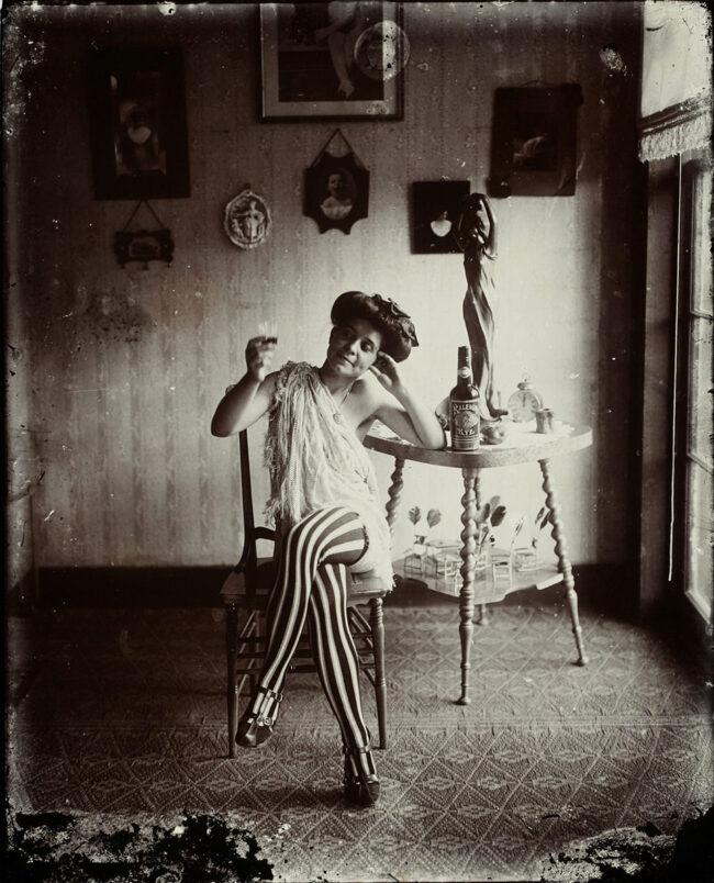 Frau sitzt lächelnd mit Whiskyglas in der Hand auf einem Stuhl
