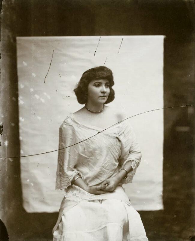 Eine Frau posiert vor einem weißen Tuch