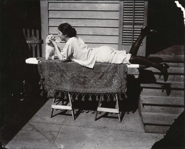 Eine Frau liegt auf einem Tisch und spielt mit einem kleinen Hund