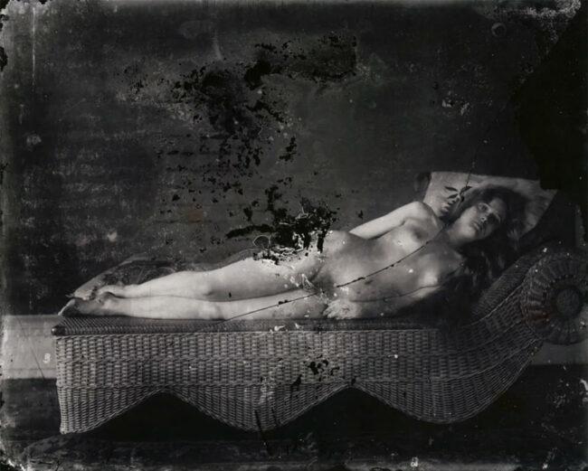 Eine nackte Frau liegt in starrer Pose auf einem Canapé