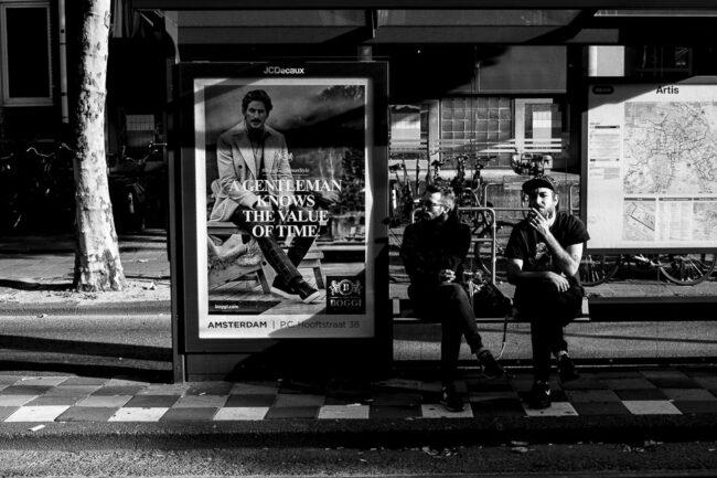 zwei Männer sitzen an einer Bushaltestelle