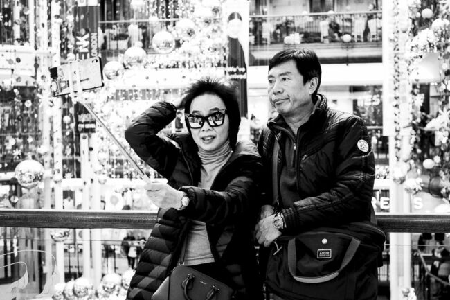 Paar mit Selfiestick in einem geschmückten Kaufhaus