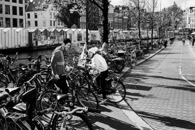 zwei Personen zwischen vielen abgestellten Fahrrädern