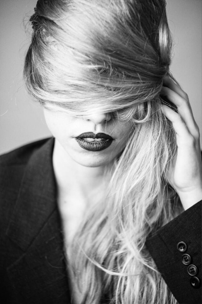 Frau verdeckt ihre Augen mit den Haaren