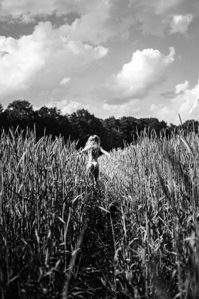 Frau rennt nackt duch ein Feld
