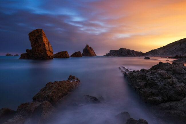 Felsen im Meer mit blau-rotem Himmel