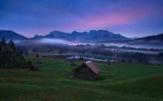 Hütte an einem See mit Nebel und Sonnenuntergang