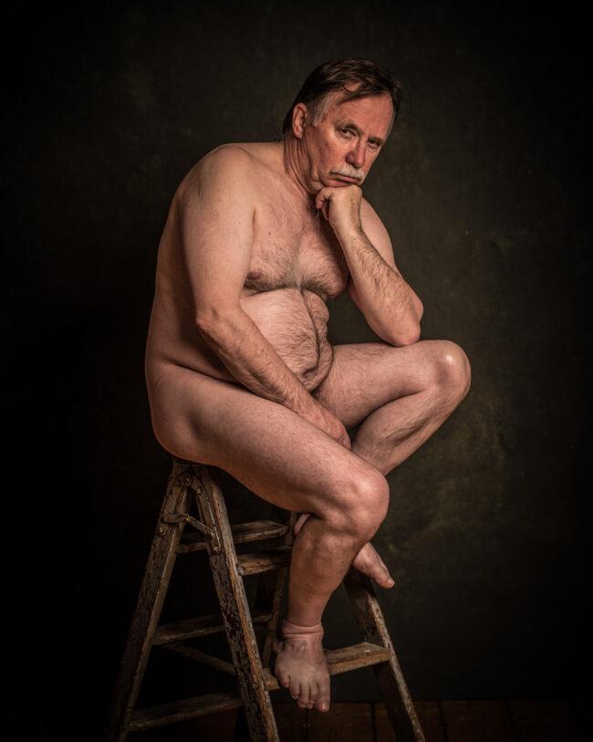 Ein nackter Mann sitzt auf einem Hocker