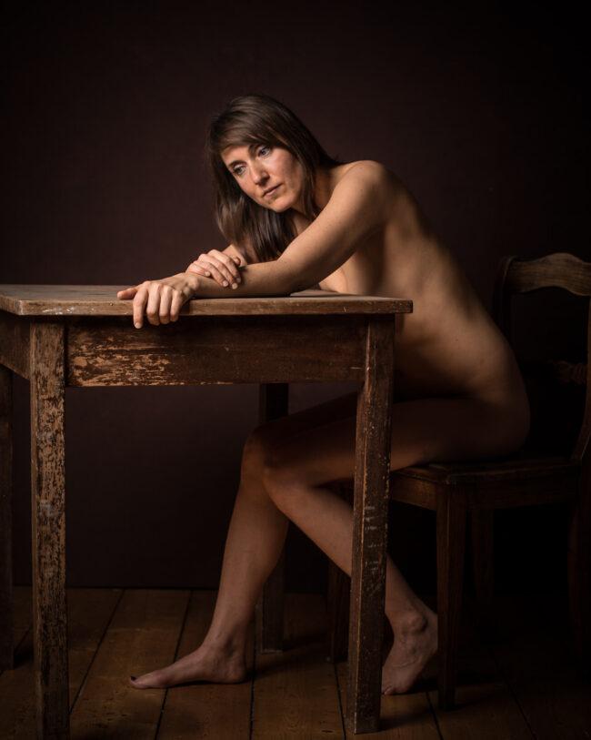 Nackte Frau an einem Tisch