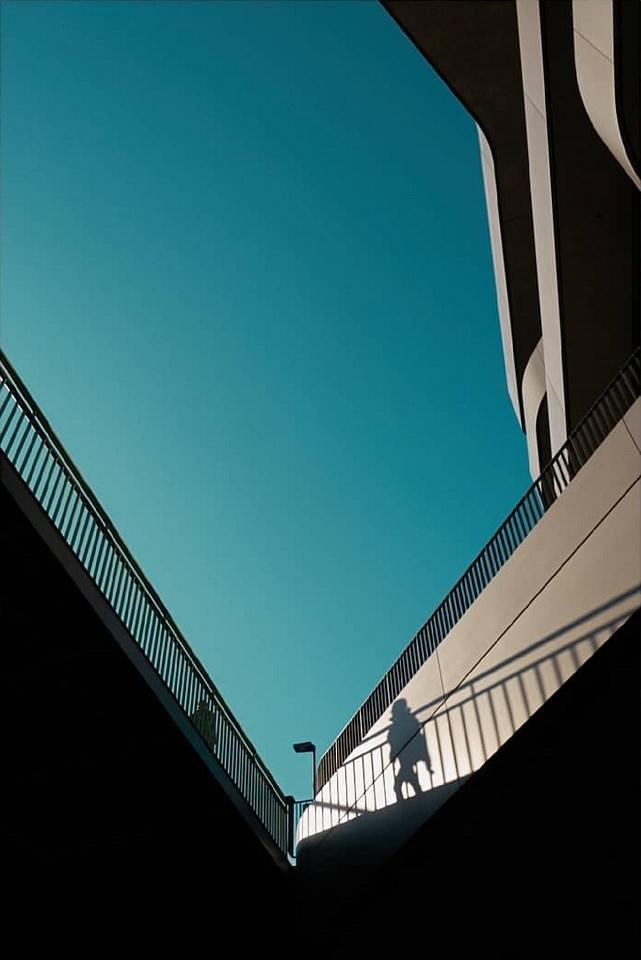 Schattenspiel mit Person auf Architektur vor blauem Himmel