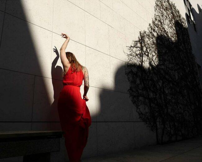 Person mit Schattenspiel an einer Fassade