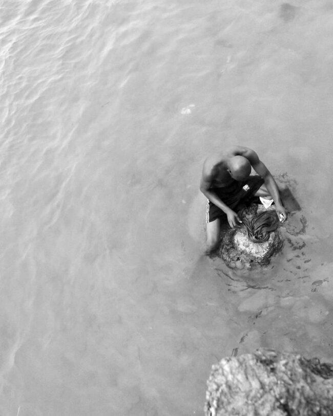 Person sitzt im Wasser und wäscht etwas auf einem Stein