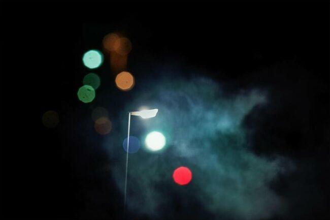 Straßenlaterne in der Nacht mit bunten Lichtkreisen