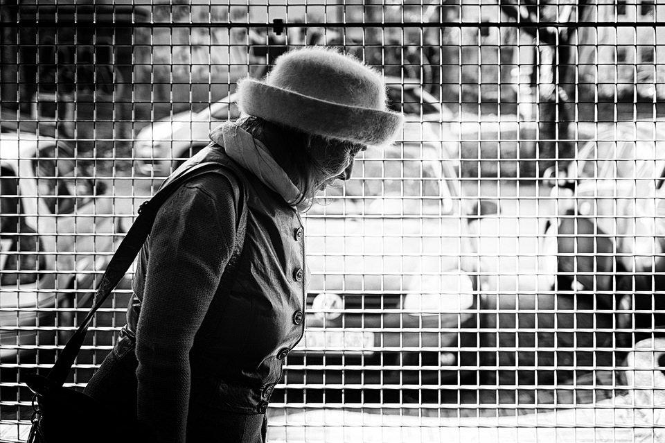 Frau vor Gitter, dahinter Autos