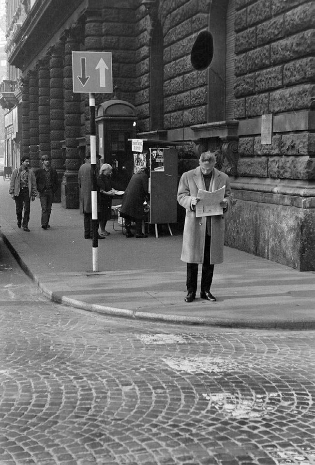 Mann steht Zeitung lesend an einer Straßenecke