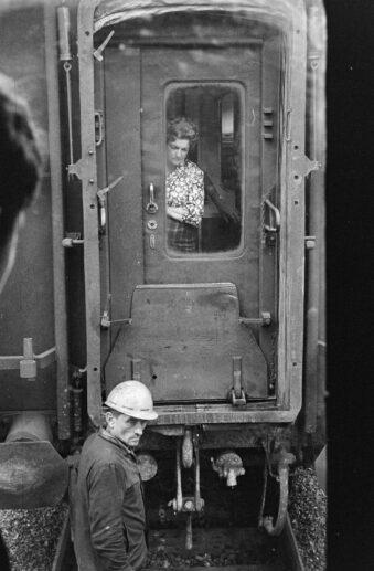 Mann vor der Tür einer Eisenbahn, durch die eine Frau blickt