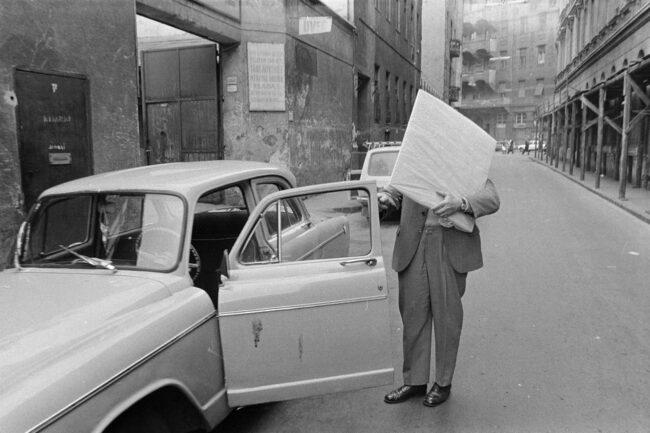 Mann an einem Auto auf der Straße