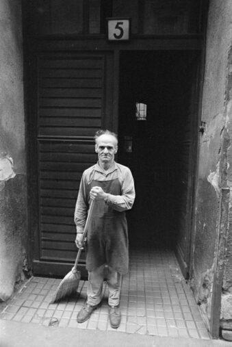 Mann mit Besen vor einer Haustür