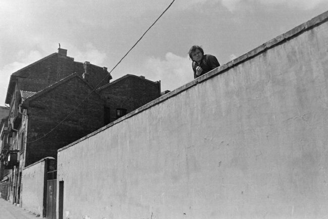 Mann schaut über eine hohe Mauer