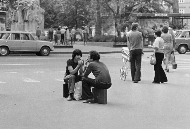 zwei Männer sitzen auf Koffern auf einer Straße