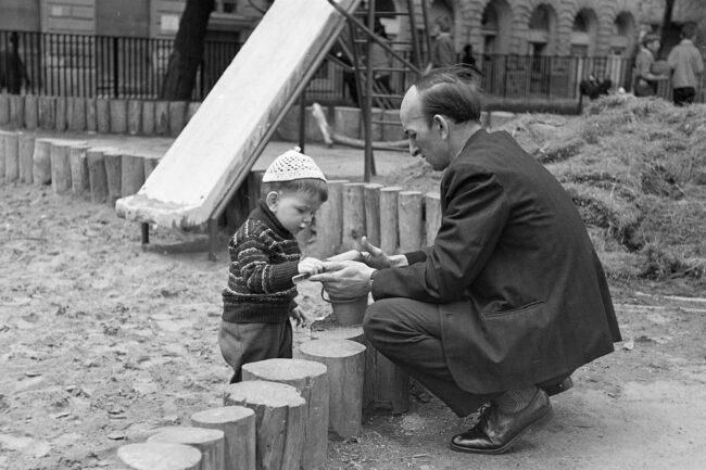 Mann mit einem Kind an einem Sandkasten