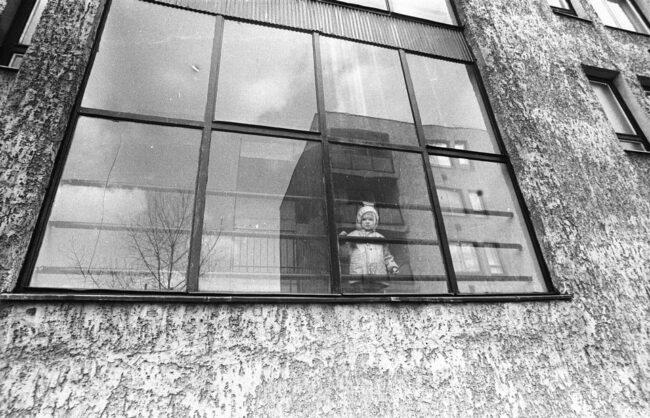 Kind schaut durch eine große Fensterfront