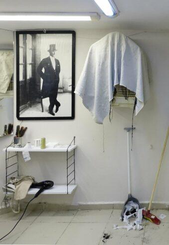 Portrait an einer Wand neben Regal und abgehängtem Spiegel