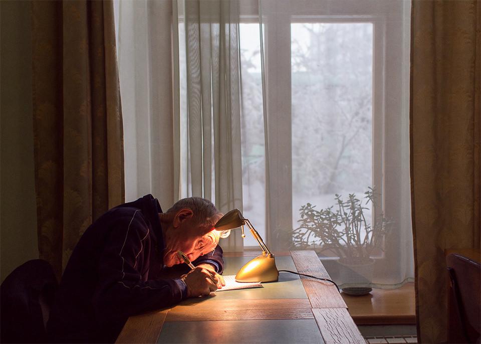 Ein Mann schreibt an einem Tisch bei einer Lampe