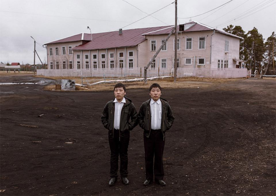Zwei Jungen posieren nebeneinander vor einem Haus