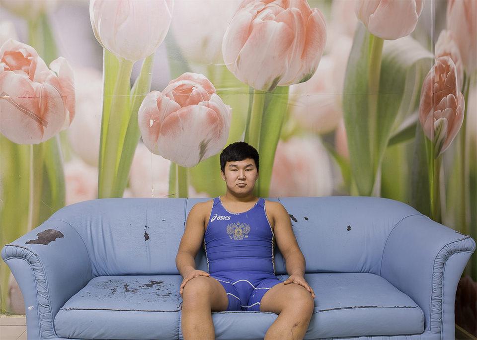 Ein Mann sitzt auf einem Sofa vor einer Tulpenwand