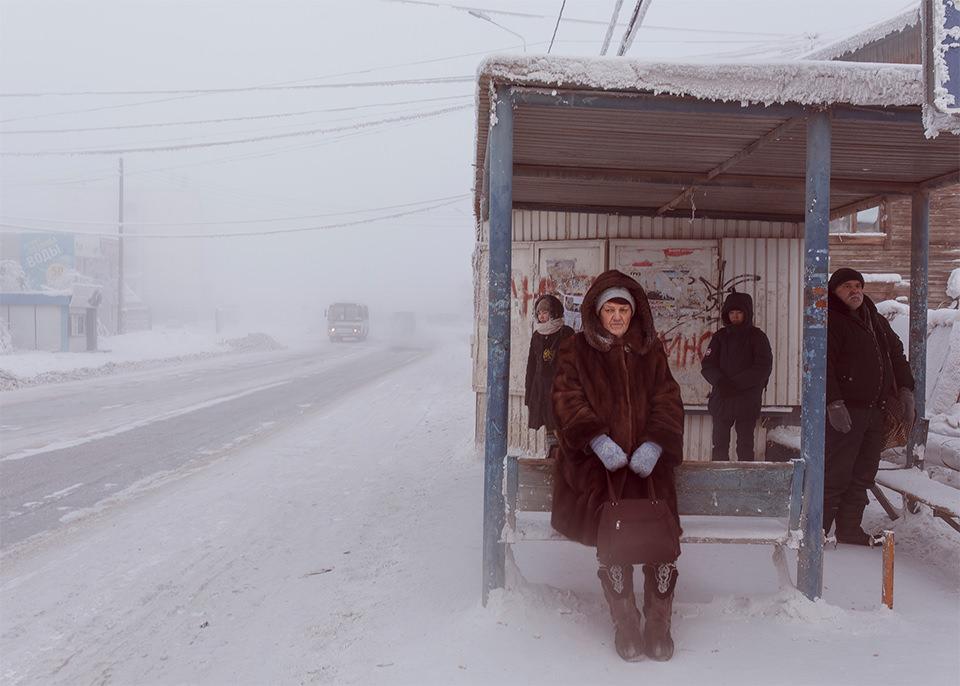 Menschen an einer Bushaltestelle im Schnee