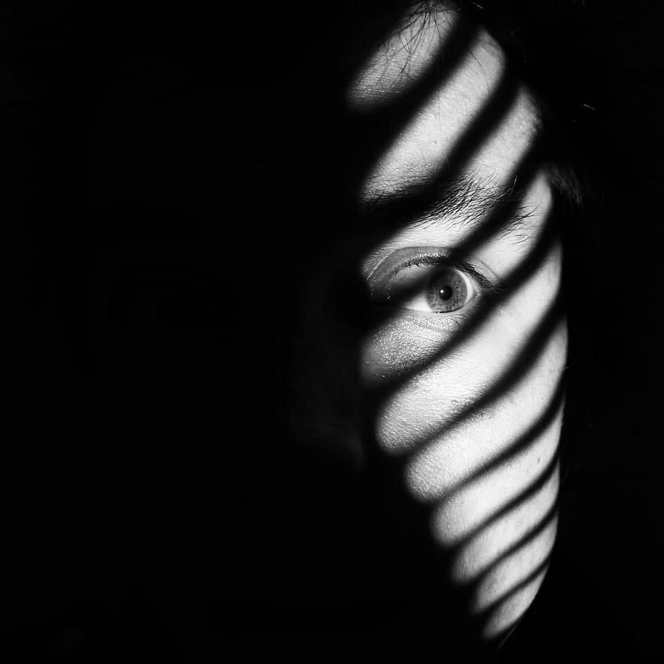 Portrait im Dunkeln mit Lichtstreifen über dem Auge
