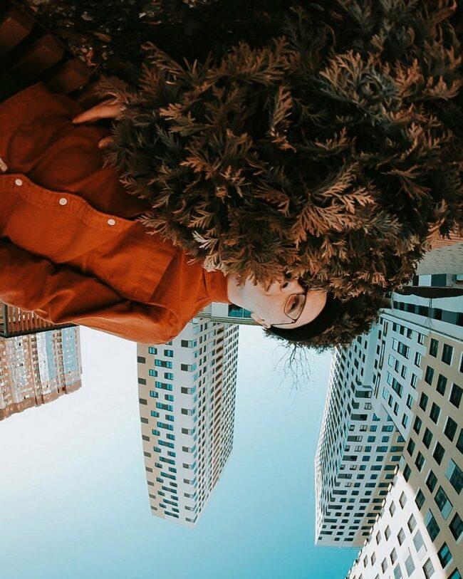 Portrait kopfüber mit Kopf in einer Thujahecke und Hochhäusern dahinter