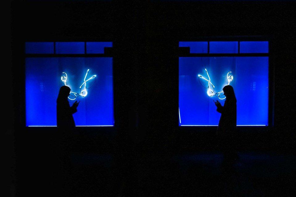 Silhouette vor blauem Neonfenster