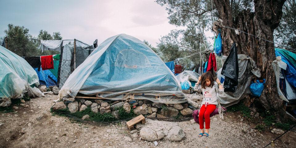 Kind auf einer selbstgemachten Schaukel vor einem Zelt