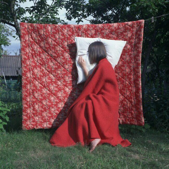 Person lehnt mit Kissen an einer aufgehängten Decke im Garten