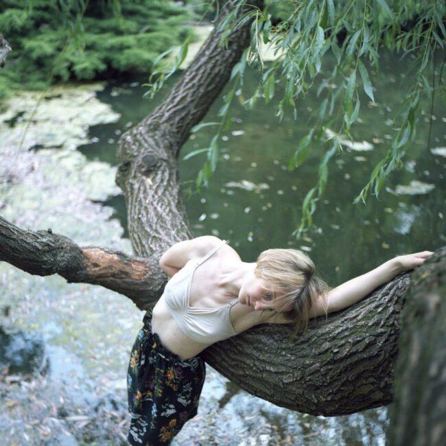 Frau in einem Teich an einen Baum gelehnt