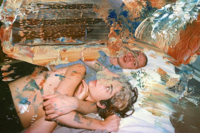 Zwei Menschen liegen in einem Bett. Das Foto ist übermalt.