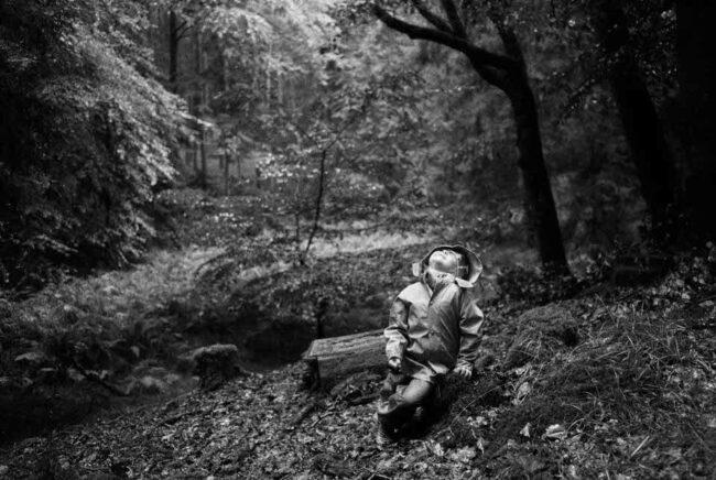 Kind im Wald fängt Regen mit dem Mund auf