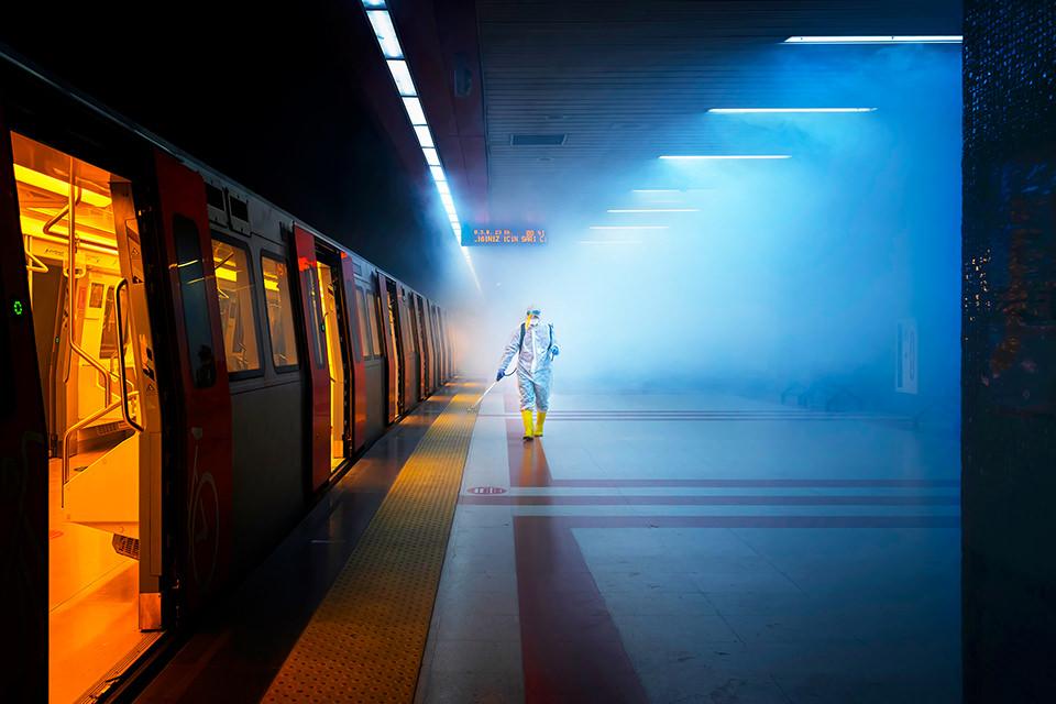 Eine Person im Schutzanzug desinfiziert eine U-Bahn-haltestelle
