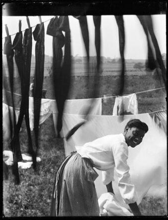 Frau beim Aufhängen von Wäsche im Freien