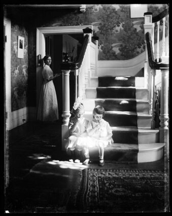 zwei Kinder sitzen auf einem Treppenabsatz, im Hintergrund des Raums dreht eine Frau sich zu ihnen um