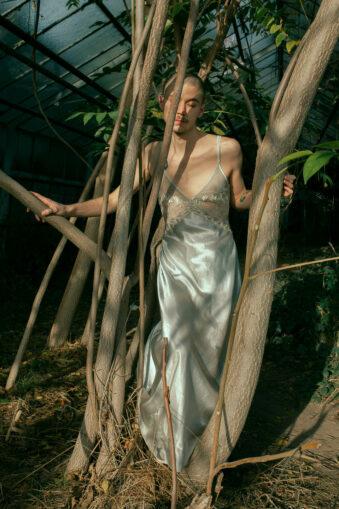 Mann im Kleid zwischen Zweigen