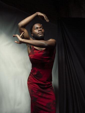 Person in rotem kleid macht tanzende Bewegungen
