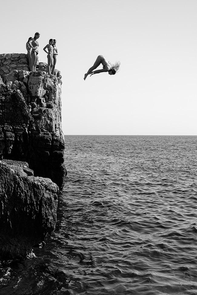 Eine Person springt von einer Klippe